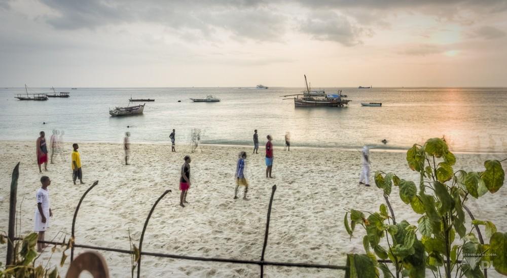 Au coucher du soleil les locaux s'activent sur la plage près du ferry de Zanzibar