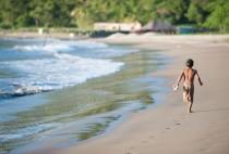 Petit tout nu qui court à la recherche d'un poisson sur la plage Marsella, Nicaragua
