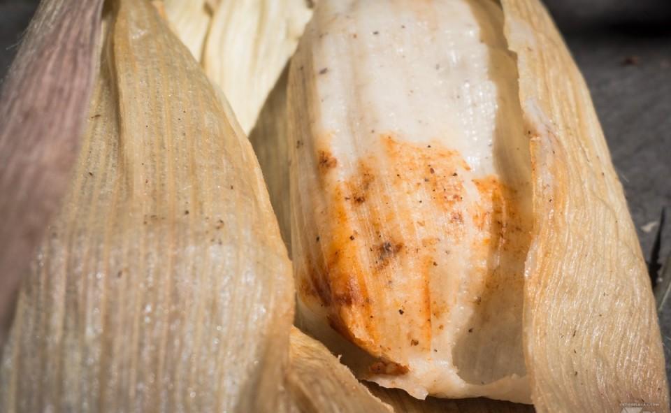 On voit ici l'intérieur du chuchitos avec la massa et le poulet à l'intérieur.