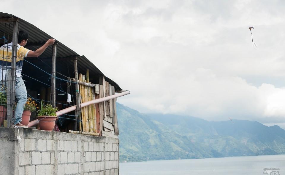 Les nombreux enfants qui jouent au cerf-volant avec la vue sur le lac Atitlán